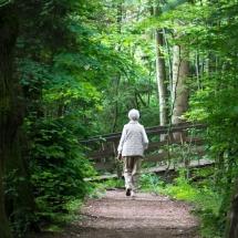 Alte Frau macht Spaziergang am Parkweg