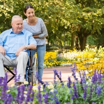 Senior man on wheelchair with home caregiver outdoors